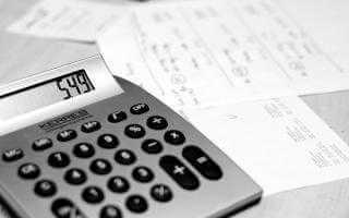 Photo of a calculator and bills on a desk.